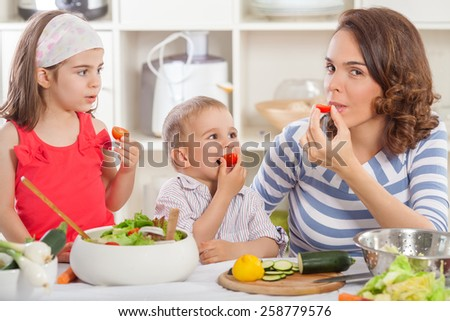Young mother teaching her children to eat vegetables
