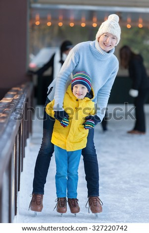young mother teaching her little son ice skating at outdoor skating rink - stock photo