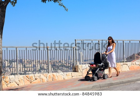 young mother walking with a stroller on the background of a big city (Jerusalem) - stock photo