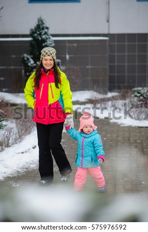 Young mother walking with her child in the courtyard of a block of flats on a winter day. She is holding a baby's hand. Earth, trees and bushes covered by snow. Daily stroll is necessary for health.
