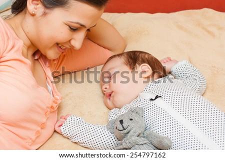 Young mother watching her baby sleeping peacefully with a teddy bear.