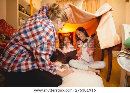 Young mother watching two daughters reading big book on floor in bedroom - stock photo