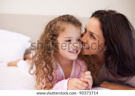 Young mother whispering into her daughters ear