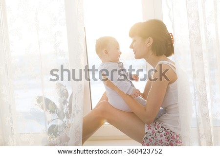Young mother with a baby in a beautiful bedroom. Happy  mother holding adorable child baby with sunrise background - stock photo