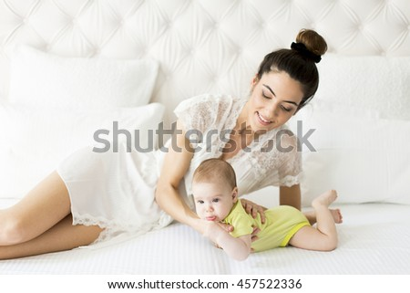 Young mother with a baby on the bed