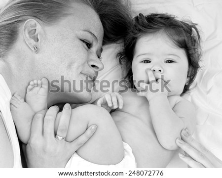 Young mother with a charming baby.Happy cheerful family. - stock photo