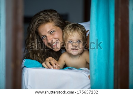 young mother with a child lying on the bed