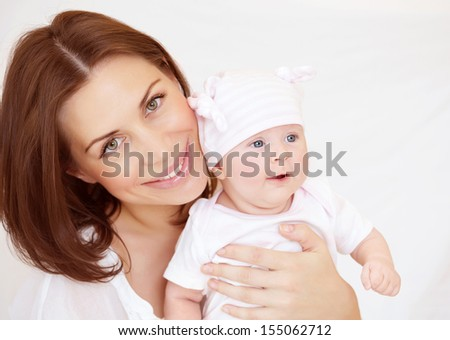Young mother with baby boy at home, funny toddler, enjoying family, healthy and happy lifestyle, loving embracing of mommy - stock photo