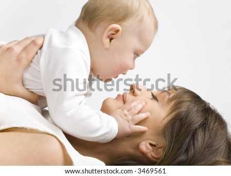 Young mother with baby boy. Lying on bed and hugging. Face to face, side view