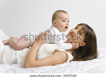 Young mother with baby boy. Lying on bed and hugging. Looking at camera, side view - stock photo