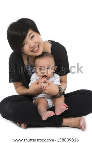 Young mother with baby boy. Sitting on white cloth. Looking at camera. front view - stock photo