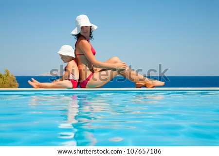 Young mother with baby daughter sitting on the edge of the pool and stare at the sea - stock photo