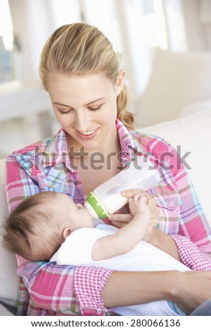 Young Mother With Baby Feeding On Sofa At Home - stock photo