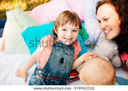 Young mother with baby having fun outdoors at picnic in the park.