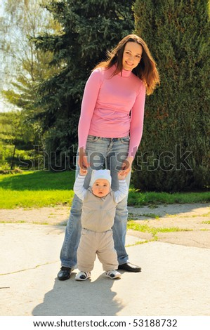 Young mother with baby in spring park - stock photo