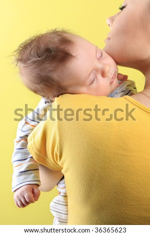 young mother with baby sleeping on shoulder - stock photo