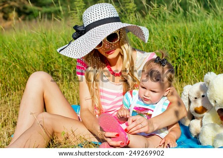 Young mother with baby sunning on the nature - stock photo