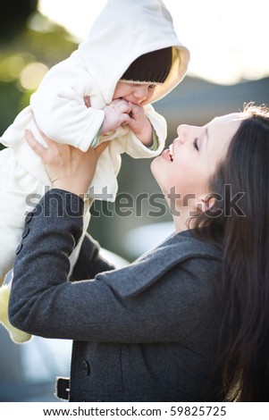 Young mother with child outside. - stock photo
