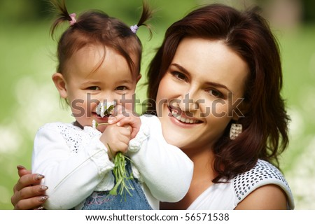 Young mother with child outside on a summer day. Focus is on the woman. - stock photo