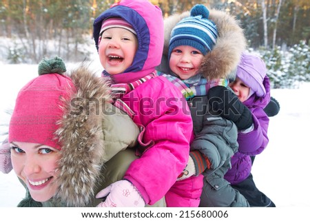 Young mother with  children playing on snow in winter time