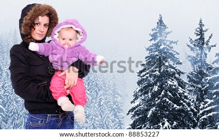 Young mother with cute baby dressed in a fur in winter mountain. Seasonal fashion shot.