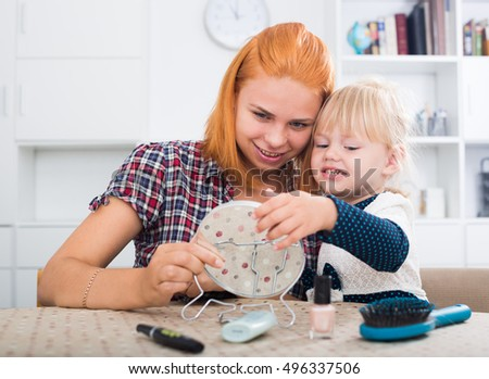 young mother with daughter looking at small mirror on table indoors