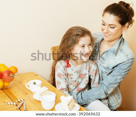 young mother with daughter on kitchen drinking tea together hugging eating celebration cake - stock photo
