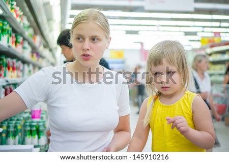Young mother with daughter select milk drinks in supermarket - stock photo