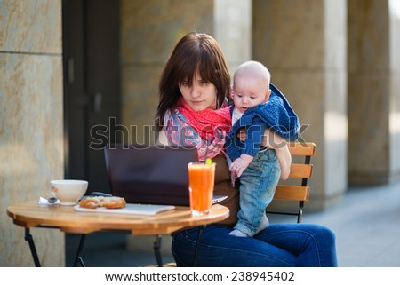 Young mother with her adorable baby boy working or studying on her laptop in cafe  - stock photo