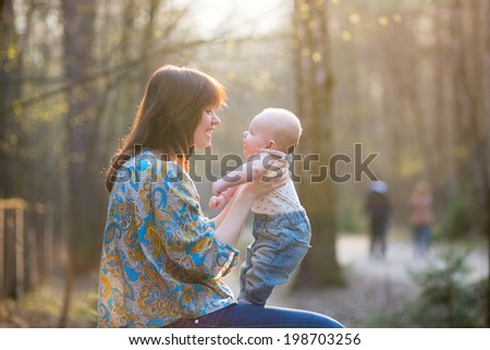 Young mother with her adorable little baby in forest - stock photo
