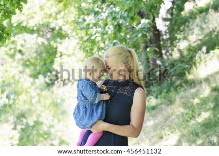 Young mother with her baby daughter in the park - stock photo
