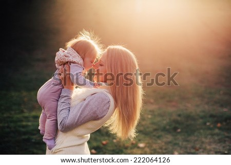 Young mother with her baby outdoor against the sun - stock photo
