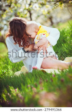 Young mother with her child sitting on grass - stock photo