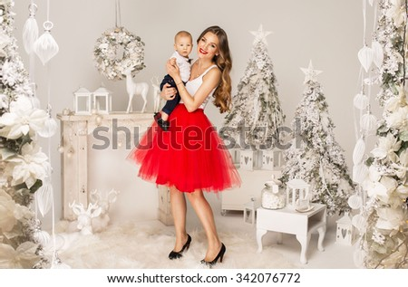 Young mother with her cute child posing in christmas scenery - stock photo