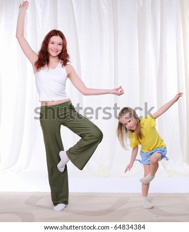 Young mother with her daughter doing sport exercises - stock photo
