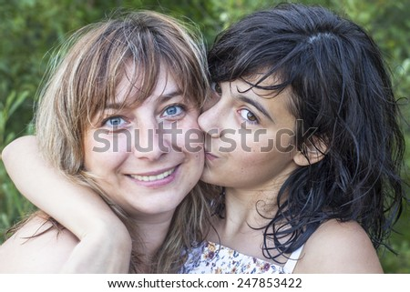 Young mother with her daughter hugging of a loving, close-up portrait. - stock photo