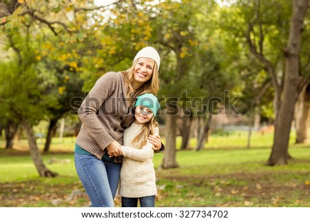 Young mother with her daughter on an autumns day