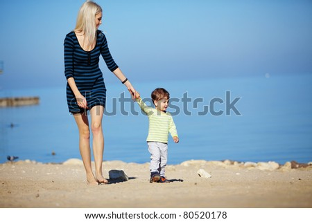 Young mother with her kid resting at the beach - stock photo