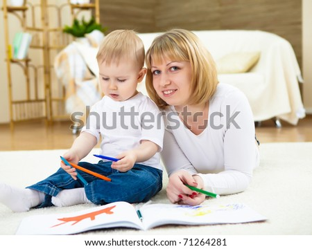 young mother with her little son at home drawing with color pencils - stock photo