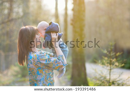 Young mother with her little son in a spring forest
