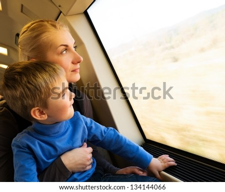 Young mother with her little son traveling on train - stock photo