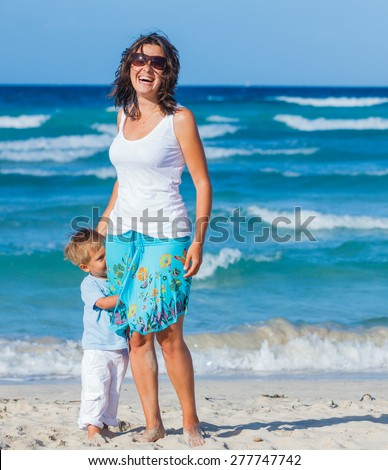 Young mother with her son on tropical beach vacation - stock photo