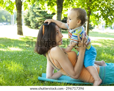 Young mother with her son playing on the grass in the Park. - stock photo