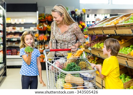 Young mother with her two children at supermarket - stock photo