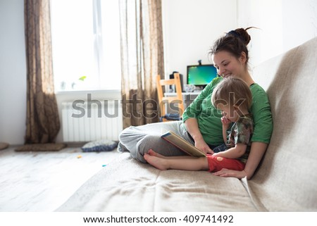 Young mother with her 2 years old little son dressed in home wear are relaxing weekend together, read book lazy morning, warm and cozy scene. Pastel colors, selective focus. - stock photo