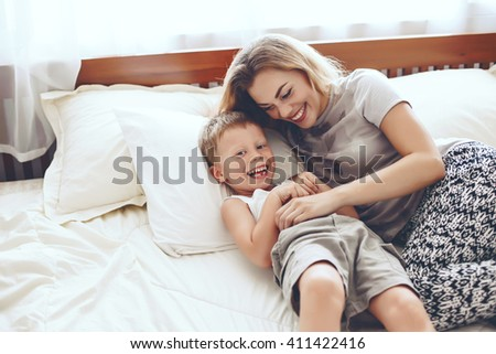 Young mother with her 6 years old little son dressed in pajamas are relaxing and playing in the bed at the weekend together, lazy morning, warm and cozy scene. - stock photo
