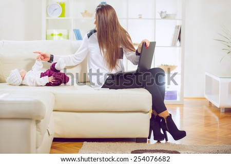 Young mother with laptop on the couch, baby lying on the couch - stock photo