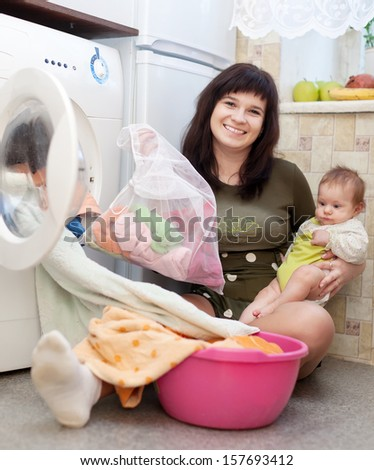 Young mother with little baby doing laundry at  home - stock photo
