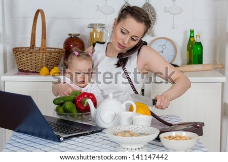 Young mother  with   little child sit at the dining table in the home kitchen. - stock photo