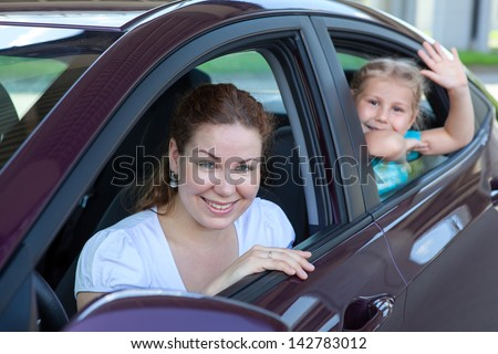 Young mother with little child sitting in land vehicle. Caucasian people - stock photo